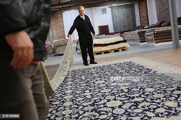 Persian 'Nain' rug is folded at the Oriental Rug Centre's main warehouse on March 17 2016 in London England The Oriental Rug Centre in North London...
