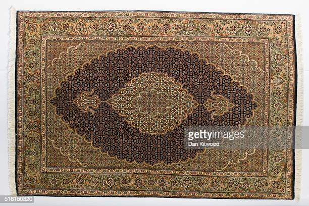 Persian 'Tabriz' rug is displayed at the Oriental Rug Centre's main warehouse on March 17 2016 in London England The Oriental Rug Centre in North...