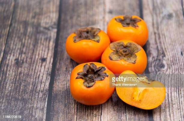 persimmon fruit on old wooden background, top view. - khaki stock pictures, royalty-free photos & images