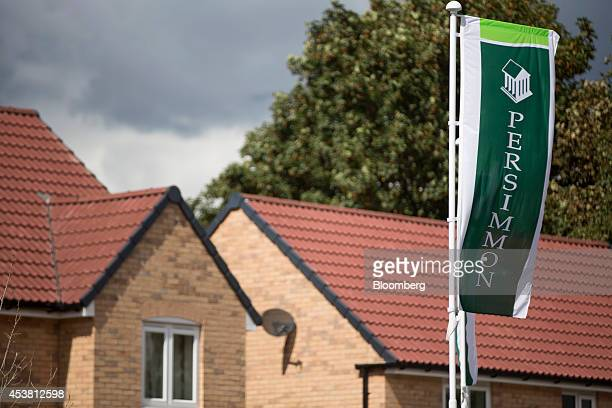 A Persimmon logo sits on a green banner as it flies near newly constructed houses at Persimmon Plc's St Andrew's Park residential housing development...
