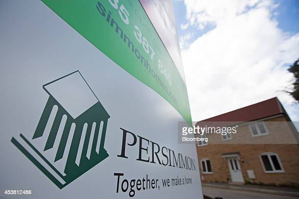 A Persimmon logo sits on a sign near newly constructed houses at Persimmon Plc's St Andrew's Park residential housing development in the Uxbridge...