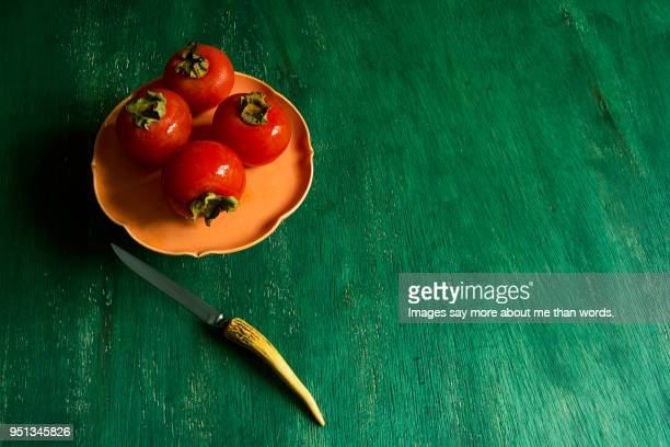 4  persimmon. over an orange serving plate. a knife. still life. - khaki stock pictures, royalty-free photos & images