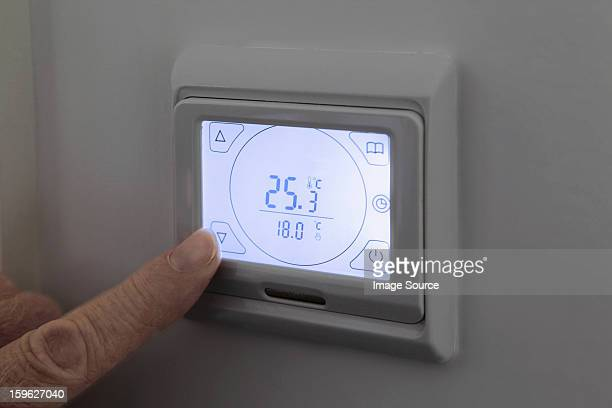 Person adjusting digital thermostat