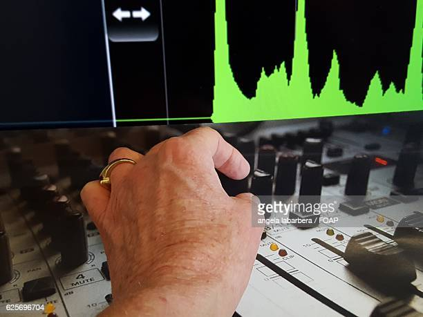 Person adjusting music equalizer on screen