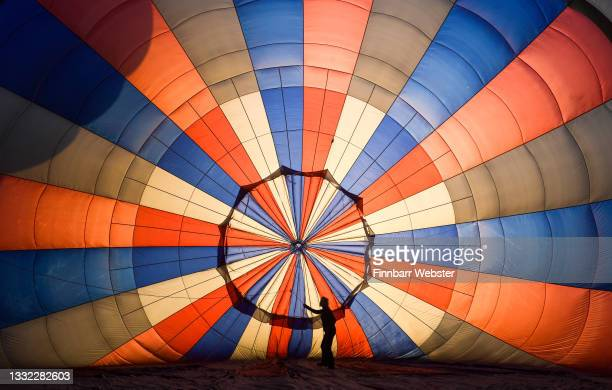 """Person adjusts some lines inside a hot-air balloon before take off on August 04, 2021 in Bristol, England. """"Fiesta Fortnight"""" takes place until..."""
