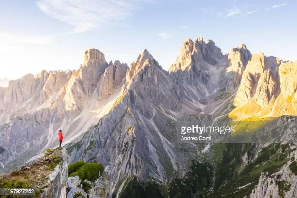 a person admiring the cadini di misurina, dolomites, veneto - natural landmark stock pictures, royalty-free photos & images