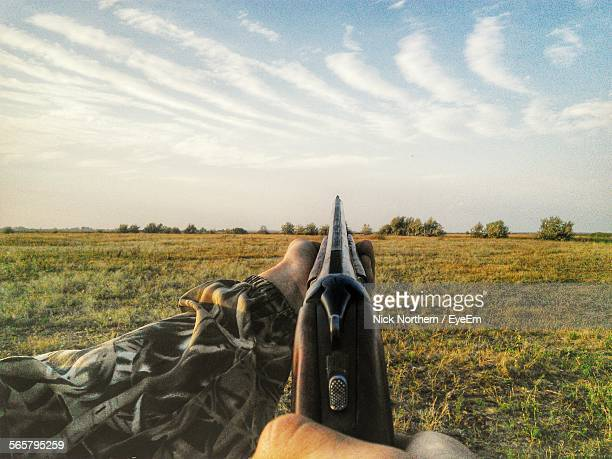 person aiming with shotgun in remote field - shotgun stock pictures, royalty-free photos & images