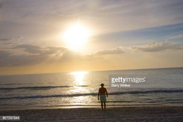 person alone walking water's edge, captiva - captiva island stock photos and pictures