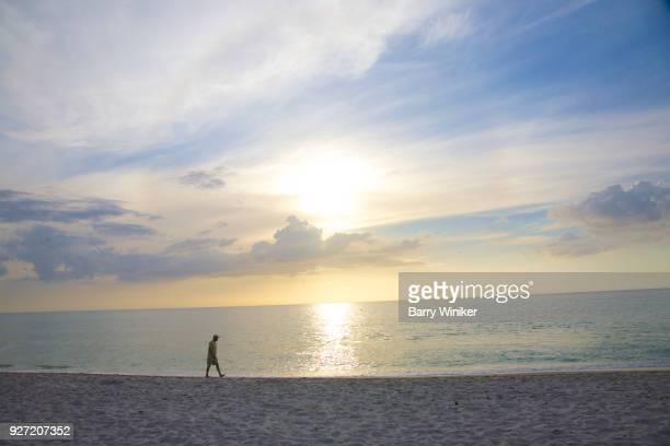 person alone walking water's edge late afternoon, captiva - captiva island stock photos and pictures