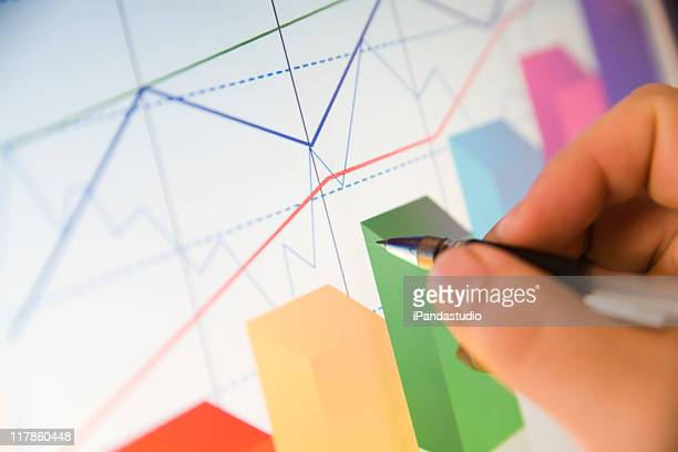 Person analyzing data in colorful line and bar graphs