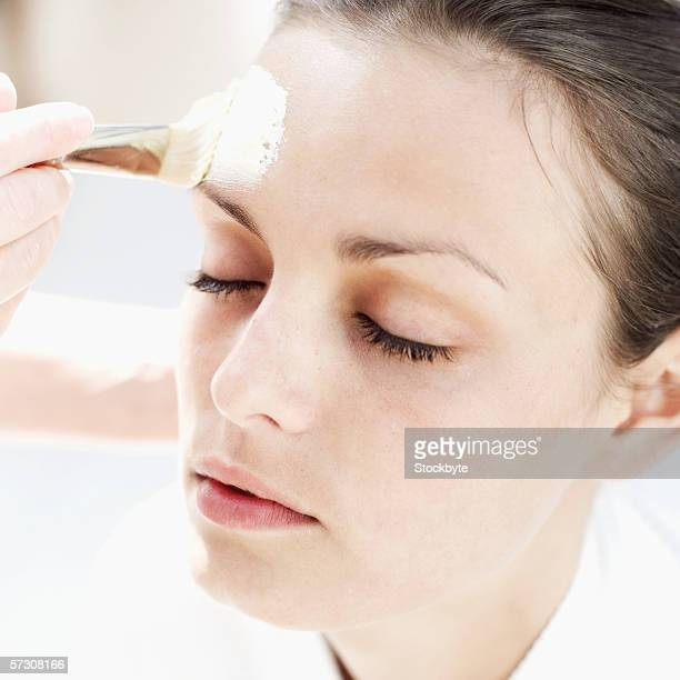 Person applying a face mask to a young woman's face