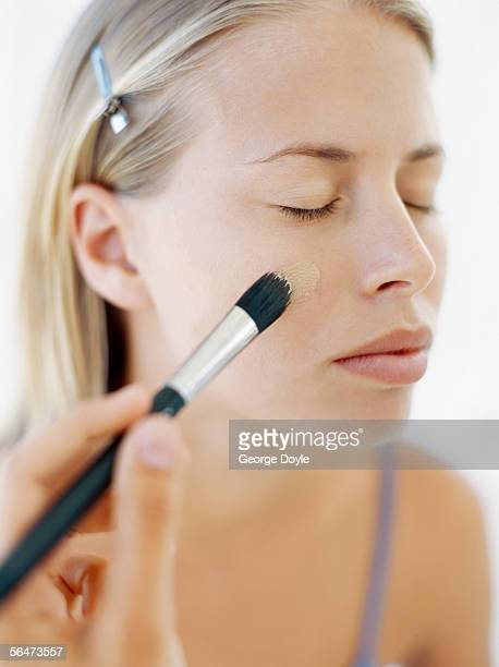 person applying blusher on the cheeks of a young woman
