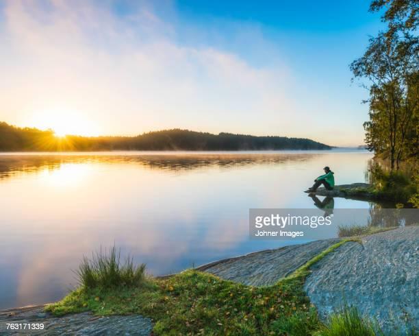 Person at lake looking at sunset