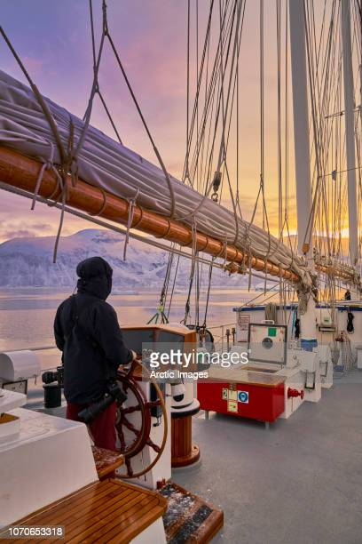 Person at ships wheel- three mast schooner, Scoresbysund, Greenland