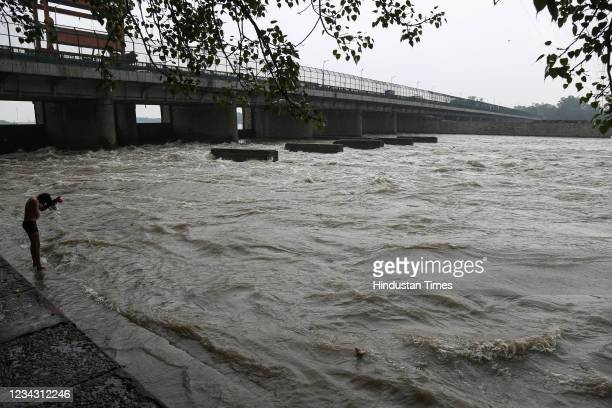 Person bathes by the banks of the Yamuna River during the monsoon, at Wazirabad, on July 29, 2021 in New Delhi, India.
