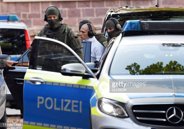 Person believed to be the suspect in the Halle shooting is escorted to a police car by policemen after landing in a helicopter at the Federal Supreme...
