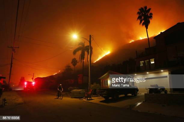 A person bicycles as a section of the Thomas Fire burns on a bluff on December 7 2017 in La Conchita California Many evacuation holdouts were forced...