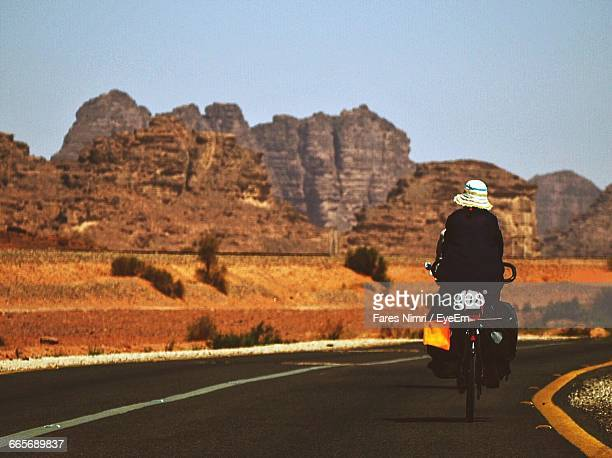 Person Bicycling On Road Against Rocky Mountains