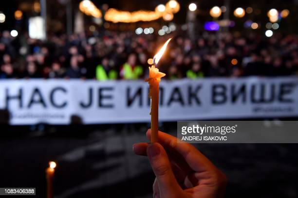 TOPSHOT A person brandishes a candle as others hold a banner reading in cyrillic Still there is more of us during a silent march in Belgrade in...