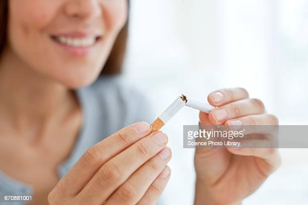 Person breaking cigarette in half