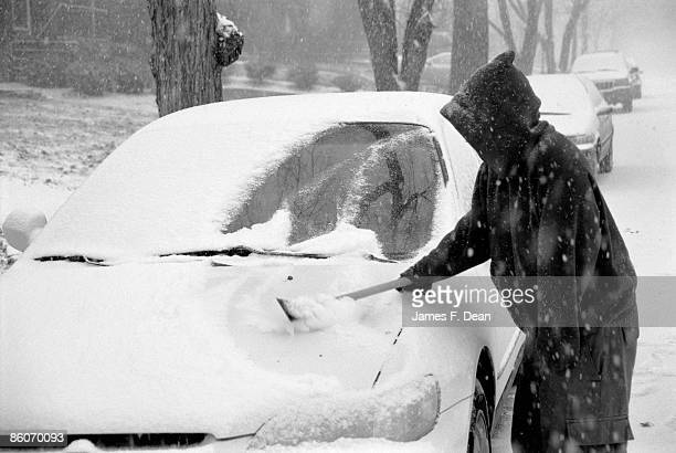 person brushing snow from car - scraping stock photos and pictures
