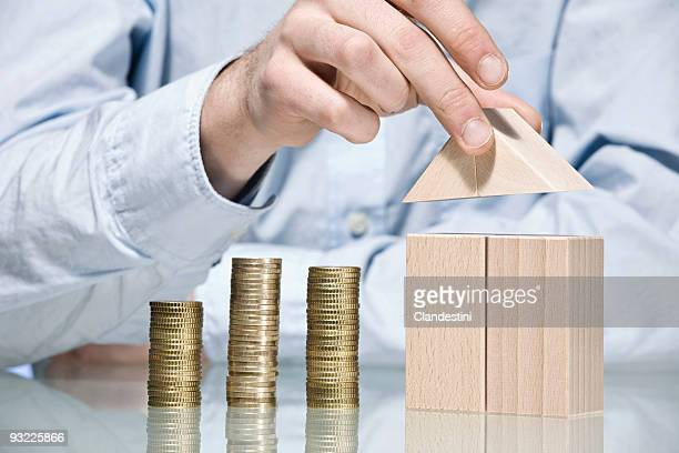 Man building house with building blocks beside stack of coins, mid section