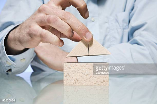 Man building house with building blocks, close-up, mid section