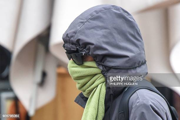 A person bundled in a hooded coat walks in Lille northern France on March 1 during a significant drop in temperatures throughout France due to a cold...