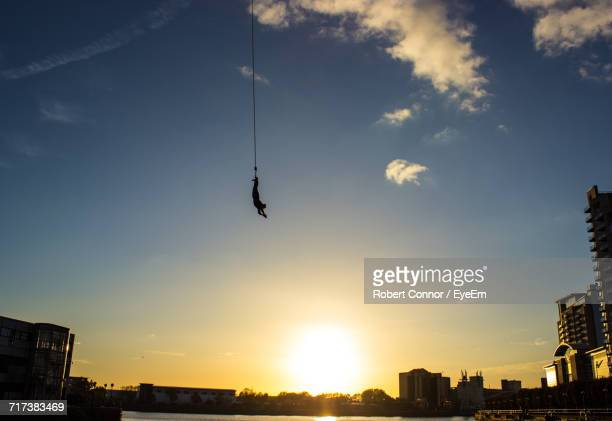 Person Bungee Jumping Over River In City Against Sky During Sunset