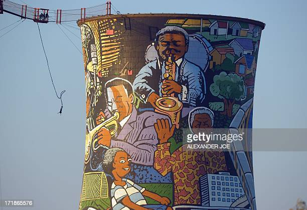 Person bungee jumps off old cooling towers in Soweto on June 29, 2013 where a mural of Nelson Mandela is visible. Mandela, who turns 95 next month,...