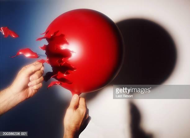 Person bursting ballon, close-up