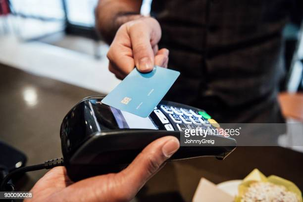 Person buying food in cafe using debit card close up
