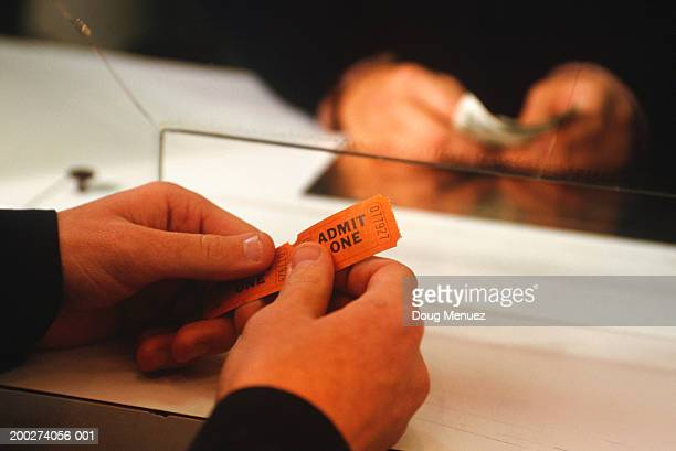 Person buying ticket at ticket-office, close-up of hands