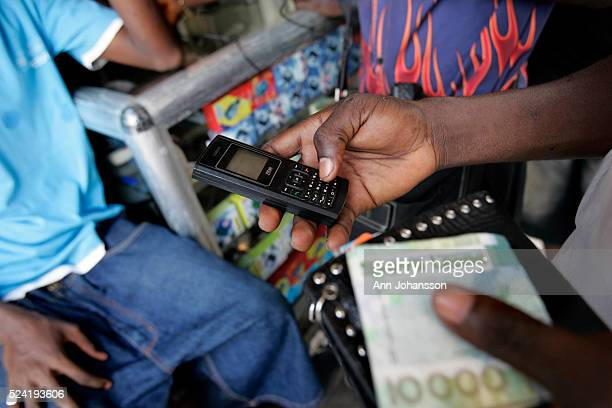 A person buys more time to use his cell phone in Freetown Sierra Leone December 8 2008
