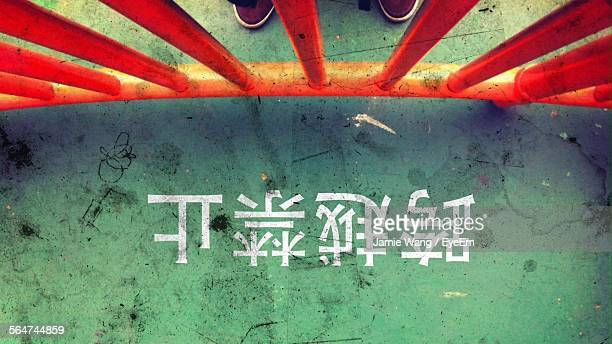 Person By Railing And Non Western Script On Street