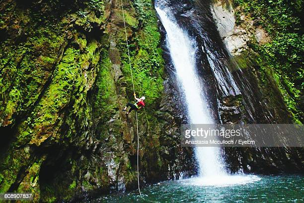 Person Canyoneering By Waterfall In Forest