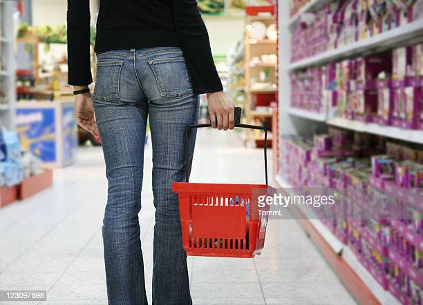A person carries a basket through a grocery store.