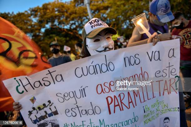 Person carries a poster that reads in Spanish against the paramilitary violence during a protest triggered by recent massacres in Samaniego and Cali...