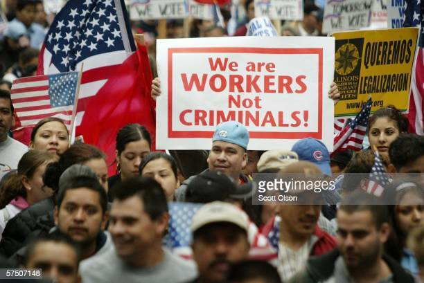 A person carries a sign which reads We Are Workers Not Criminals as other immigrant rights supporters march through downtown May 1 2006 in Chicago...