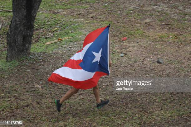 A person carries the Puerto Rican flag as they join with other people celebrating the ouster of Ricardo Rossello the Governor of Puerto Rico on July...