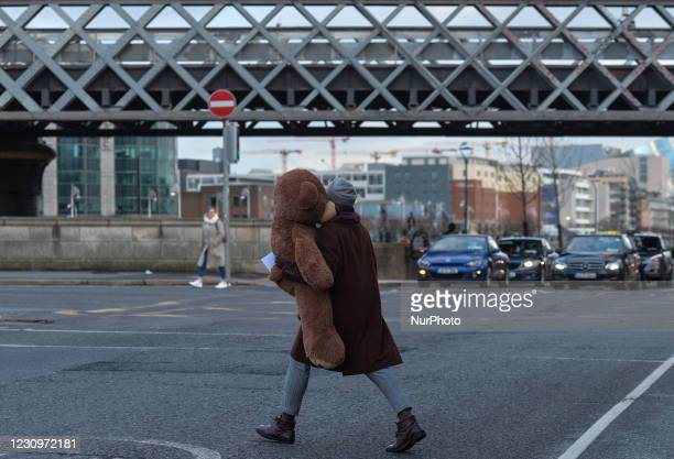 Person carrying a large teddy bear in Dublin city center during Level 5 Covid-19 lockdown. On Thursday, 4 February in Dublin, Ireland.