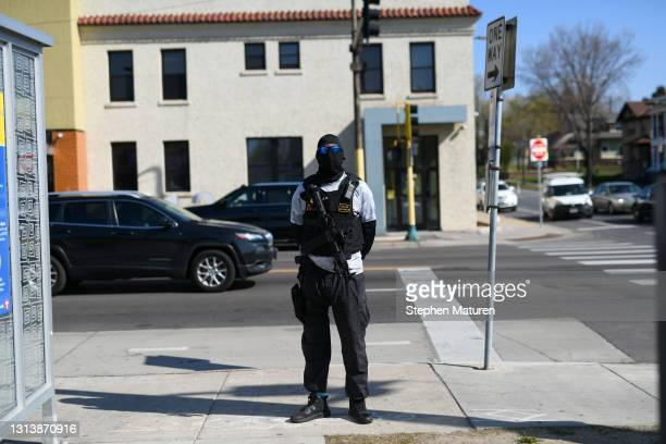 Person carrying a long rifle stands on the sidewalk during a funeral held for Daunte Wright at Shiloh Temple International Ministries on April 22,...