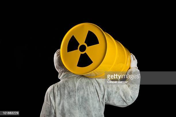A Person Carrying A Radioactive Barrel
