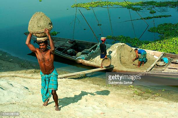 Person carrying sand on the bank of river in Bangladesh