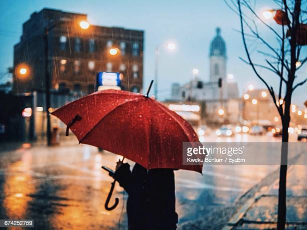 person carrying umbrella standing on city street during rainy season - umbrella stock photos and pictures