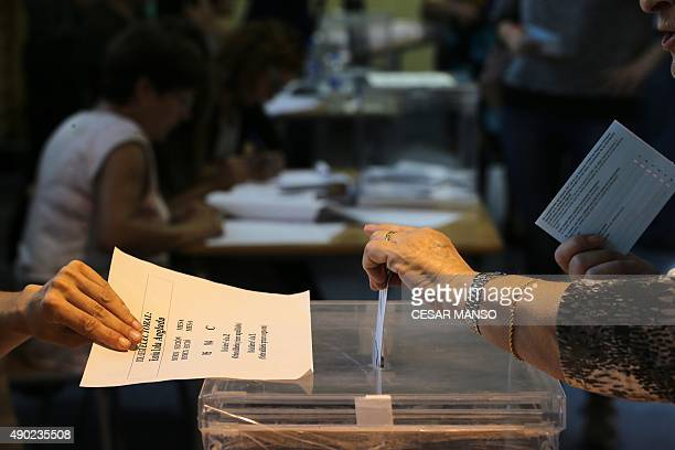 A person casts their ballots for the regional election at a polling station in Badalona on September 27 2015 After an emotional climax to campaigning...