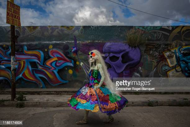 A person characterized by a PreHispanic Death walks addresses a troupe in the streets of Oaxaca as part of the 'Day of the Dead' celebrations on...