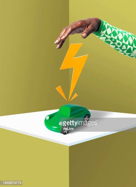 person charging car with electricity - one mature woman only stock pictures, royalty-free photos & images