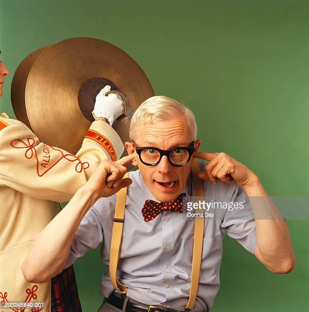 Person clanging cymbals behind senior man sticking fingers in ears, (Portrait)