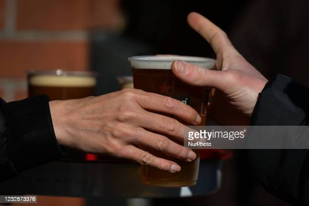 Person collecting a pint of lager beer in a plastic cup from the pub in Dublin's city center. On Thursday, 13 May 2021, in Dublin, Ireland.